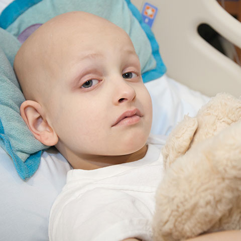 Child with stuffed animal in hospital bed