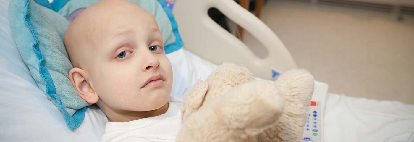 Girl in hospital bed with stuffed animal